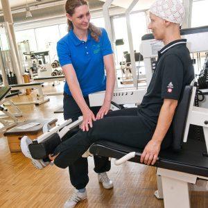 Eine Krebspatientin lässt sich im Fitnessraum von einer Trainerin bei Beinstrecker-Übungen anleiten