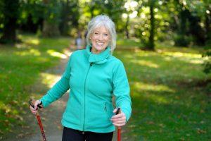 Fitte Dame über 60 mit Walking-Stöcken im Grünen